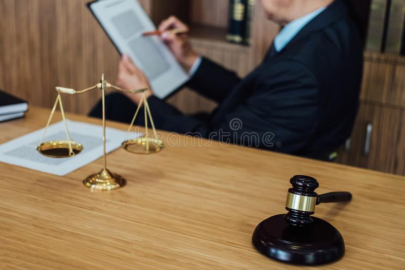 Gavel on wooden table and Lawyer or Judge working with agreement in Courtroom theme, Justice and Law concept.  stock images
