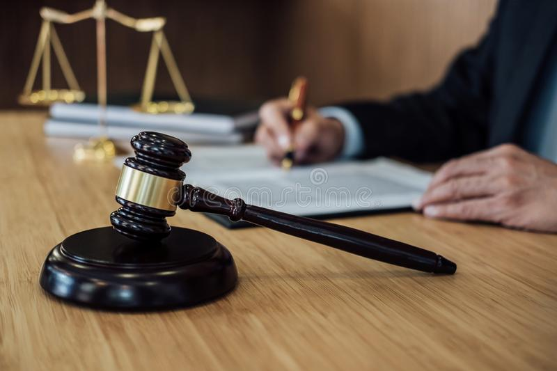 Gavel on wooden table and Lawyer or Judge working with agreement in Courtroom theme, Justice and Law concept.  royalty free stock photos