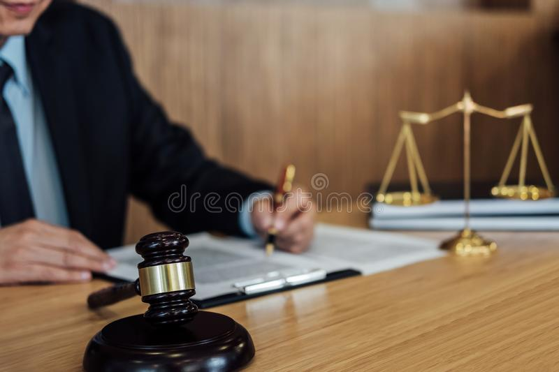 Gavel on wooden table and Lawyer or Judge working with agreement in Courtroom theme, Justice and Law concept.  stock image