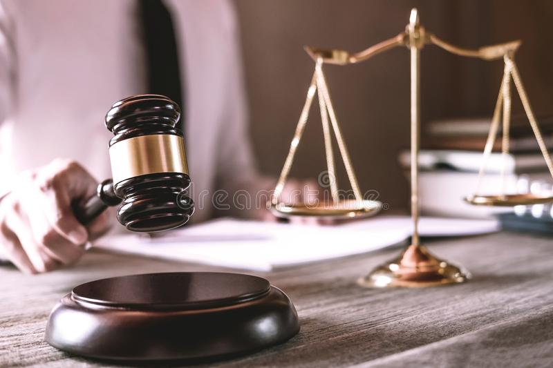 Gavel on wooden table and Lawyer or Judge working with agreement in Courtroom theme, Justice and Law concept.  royalty free stock photo