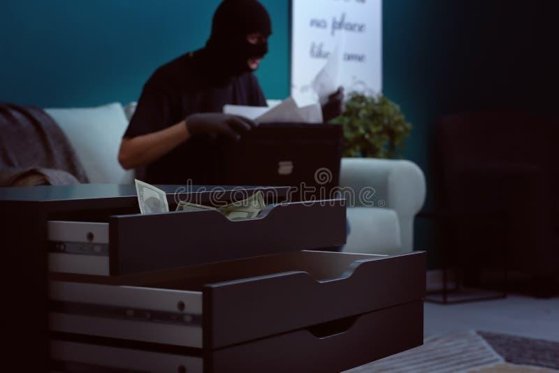Gaveta aberta com dinheiro e o ladrão masculino dentro fotografia de stock