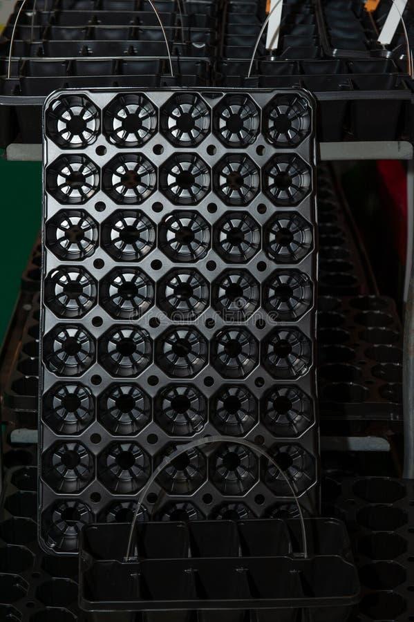 Gavetas plásticas pretas para plântulas crescentes para estufas e o jardim urbano Venda das gavetas do estoque imagens de stock