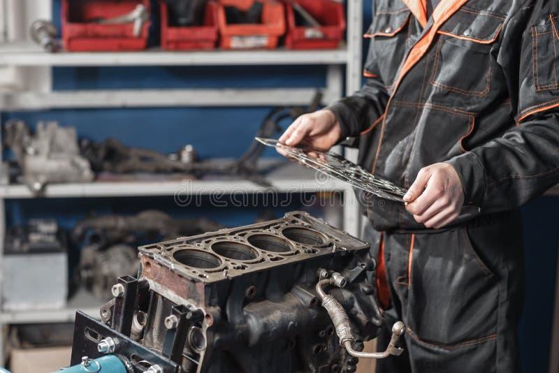 Gaxeta da selagem disponivel O mecânico desmonta o veículo do motor do bloco Motor em um suporte do reparo com pistão e fotografia de stock royalty free