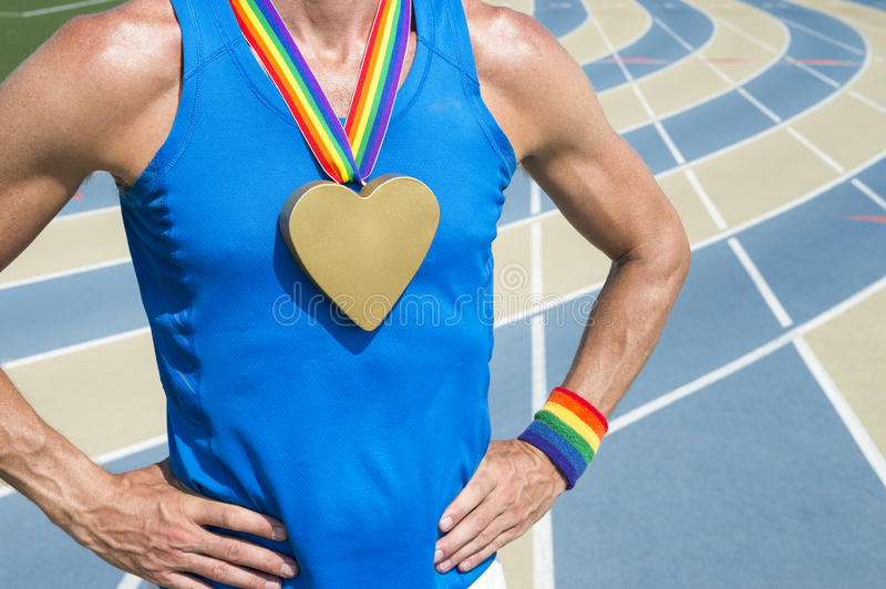 Gay Athlete Heart Gold Medal Running Track. Gay athlete standing with heart gold medal and rainbow ribbons at a running track stock image