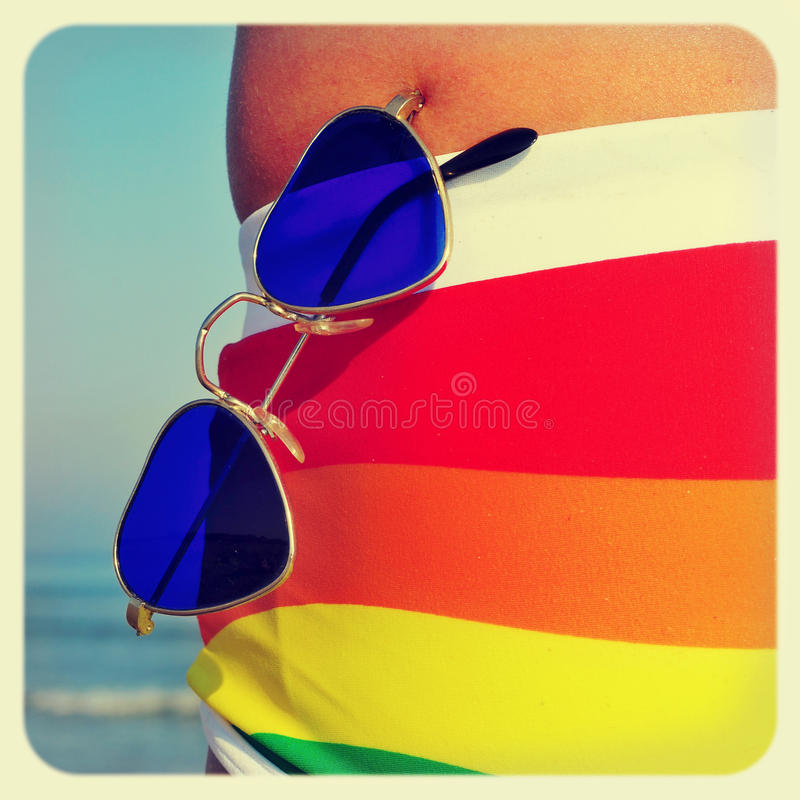 Gay beach. Someone wearing a rainbow swimsuit and heart-shaped sunglasses on the beach, with a retro effect royalty free stock images