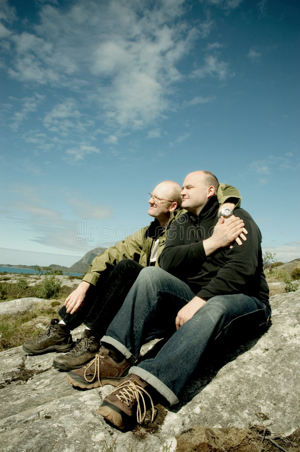 Gay couple. Sitting on rocks enjoying the sun
