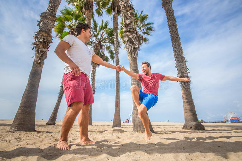 Gay couple dancing on the beach. Gay couple dancing and having fun on the beach - Homosexual partners celebrating and having party outdoors royalty free stock image