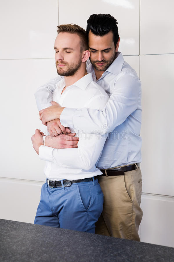 Gay couple with eyes closed hugging stock photos