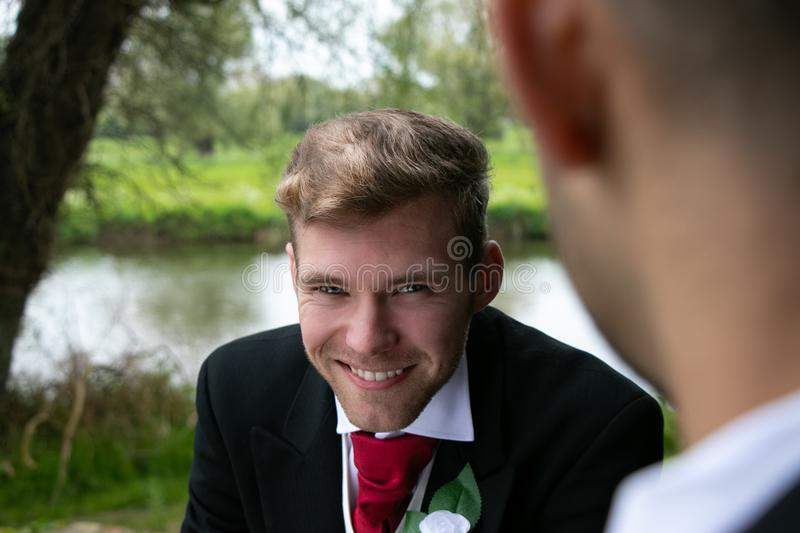 Gay couple of grooms pose for photographs by a lake on their wedding day stock images
