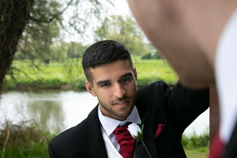 Gay couple of grooms pose for photographs by a lake on their wedding day stock photography