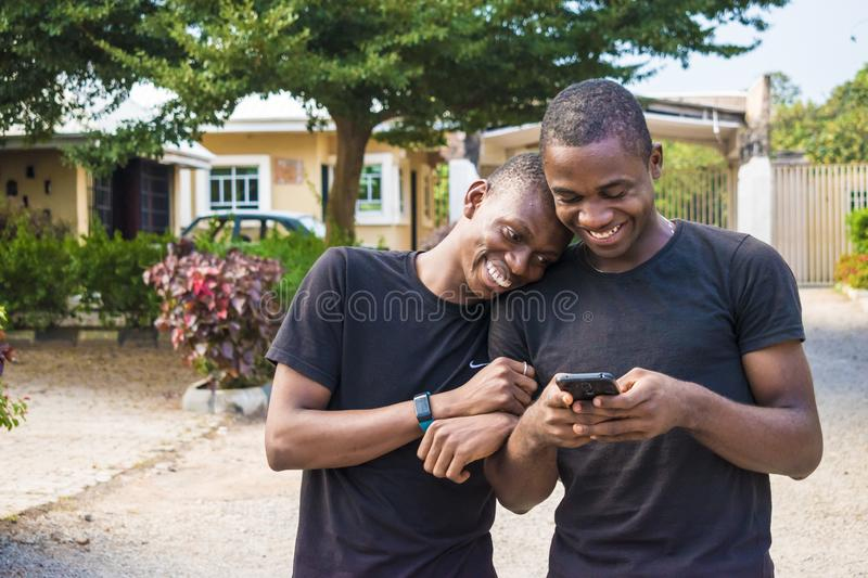 gay couple laughing together while using a phone together. two young black men walking and holding each other laughing together stock images