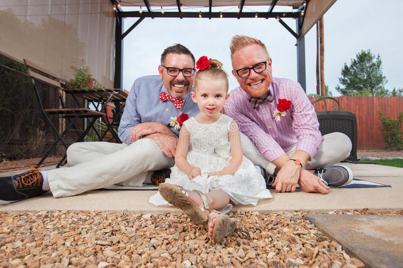 Gay Couple with Little Girl. Happy same sex couple sitting with daughter outdoors stock photo