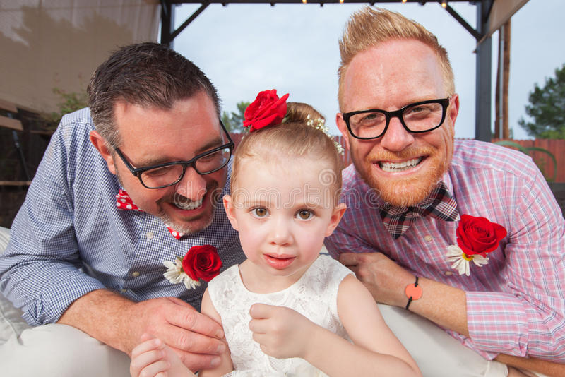 Gay Couple with Little Girl. Smiling gay couple with daughter sitting outdoors royalty free stock image