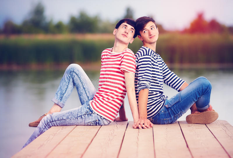 Gay couple in love on river bank royalty free stock photo