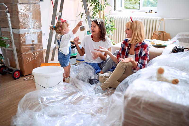 Gay couple moving in new house with a toddler girl stock photo