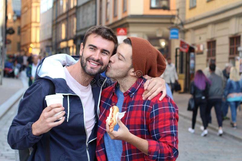 Gay couple passionately kissing on the street royalty free stock images