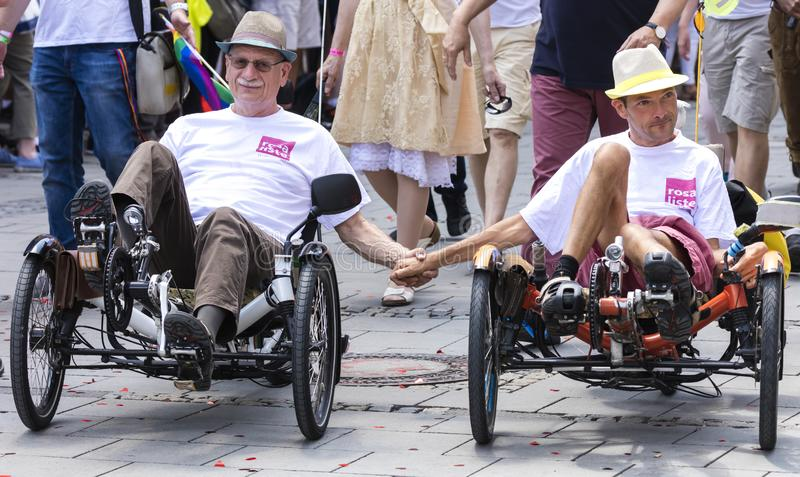A gay couple riding the recumbent tricycle and holding hands  attending the Gay Pride parade in Munich. 2018: A gay couple riding the recumbent tricycle and stock photography
