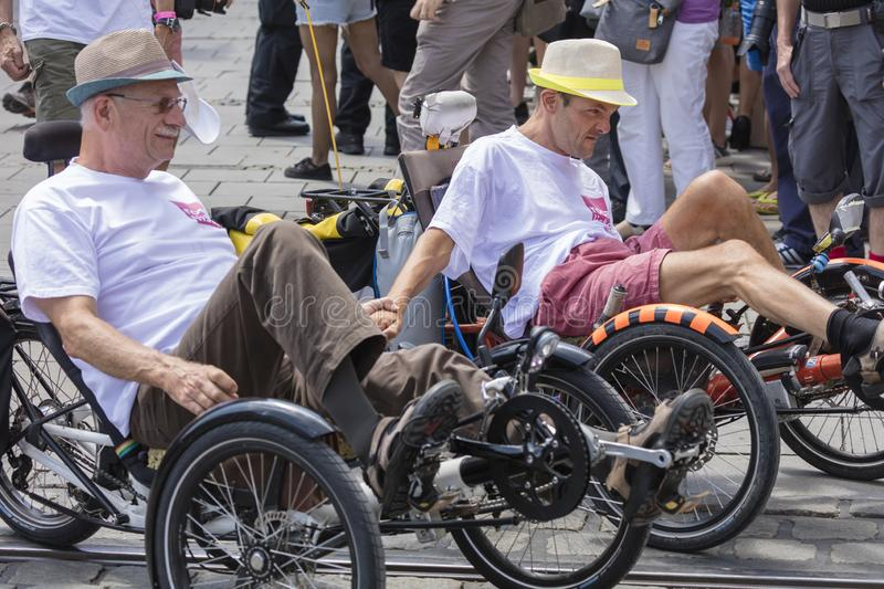 A gay couple riding the recumbent tricycle and holding hands  attending the Gay Pride parade in Munich. 2018: A gay couple riding the recumbent tricycle and royalty free stock photo
