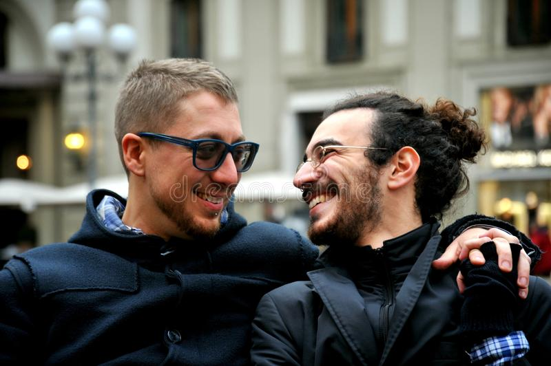 Gay couple smiling on the streets of Florence , Italy. Gay couple on the streets of Florence , Italy laughing and smiling at each other in love . Love is love royalty free stock images