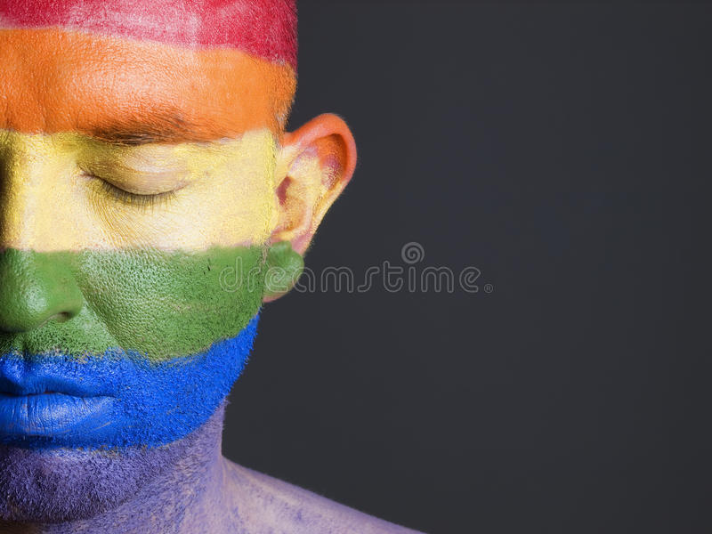 Gay flag painted on face man closed eyes. stock photo