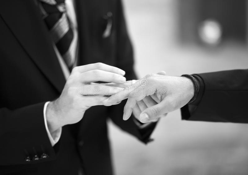 Gay LGBT wedding ceremony. Gay LGBT wedding grooms in suits holding hands in civil same sex homosexual marriage ceremony service royalty free stock photo