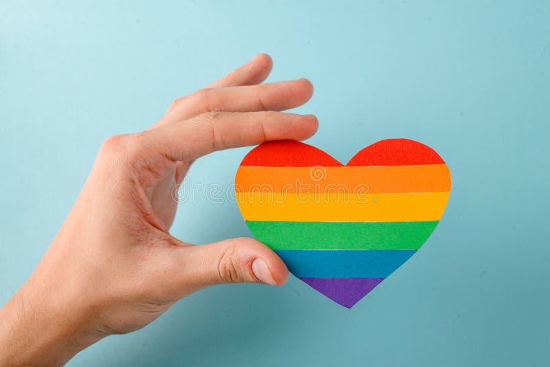 Gay llevando a cabo un corazón del arco iris fotos de archivo