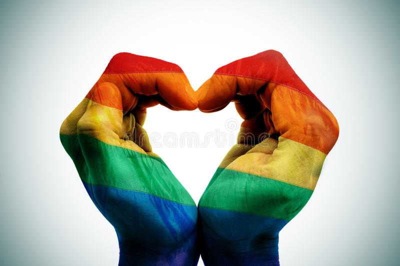 Gay love. Man hands patterned as the rainbow flag forming a heart, symbolizing gay love royalty free stock images