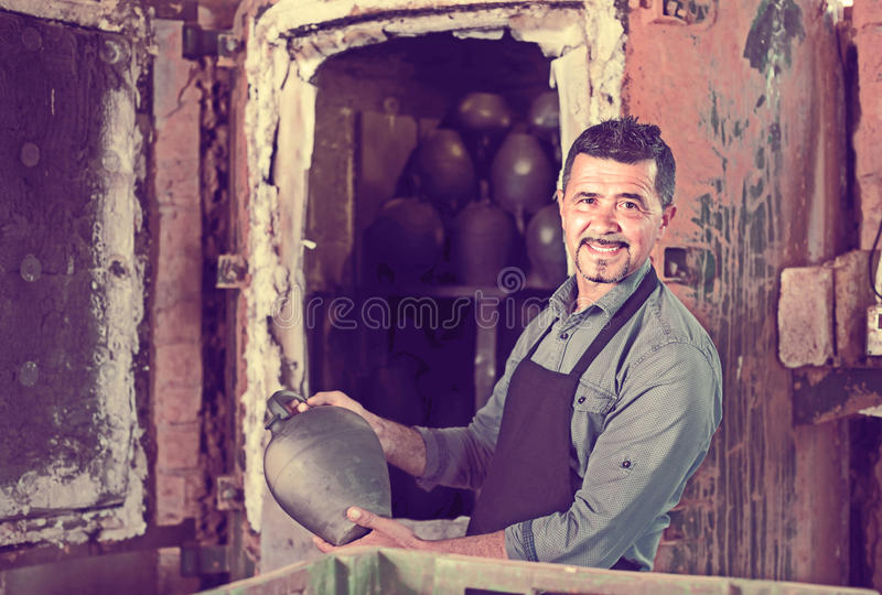Gay male with black-glazed ceramic vase standing close to kiln. Portrait of gay male artisan with black-glazed ceramic vase standing close to kiln royalty free stock photo