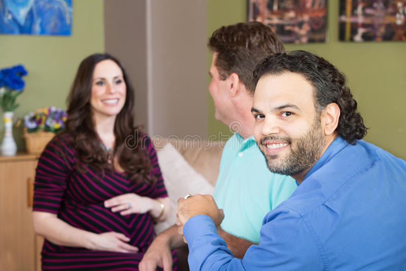 Gay Man with Partner and Pregnant Woman. Smiling gay men and partner with surrogate mother royalty free stock photography