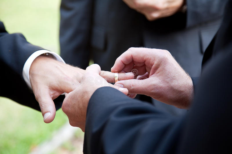 Gay Marriage - With This Ring. One groom placing the ring on another man's finger during gay wedding