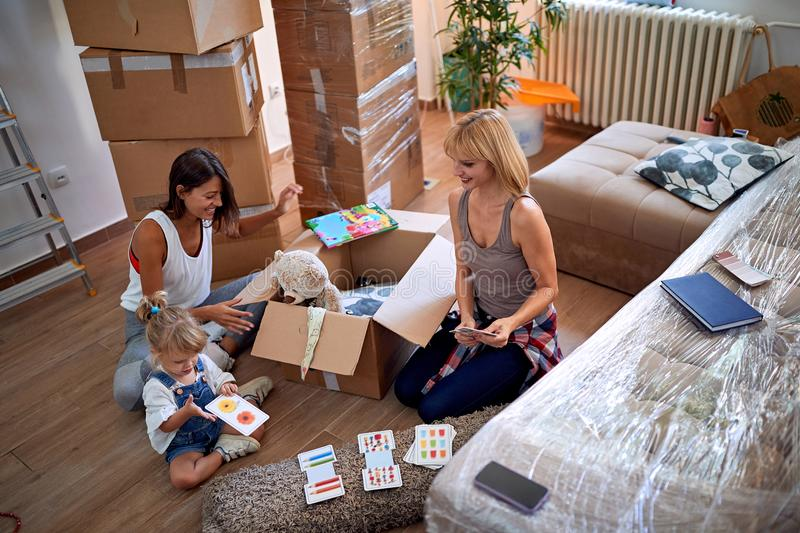 Gay mothers with a toddler girl moving in new home royalty free stock images
