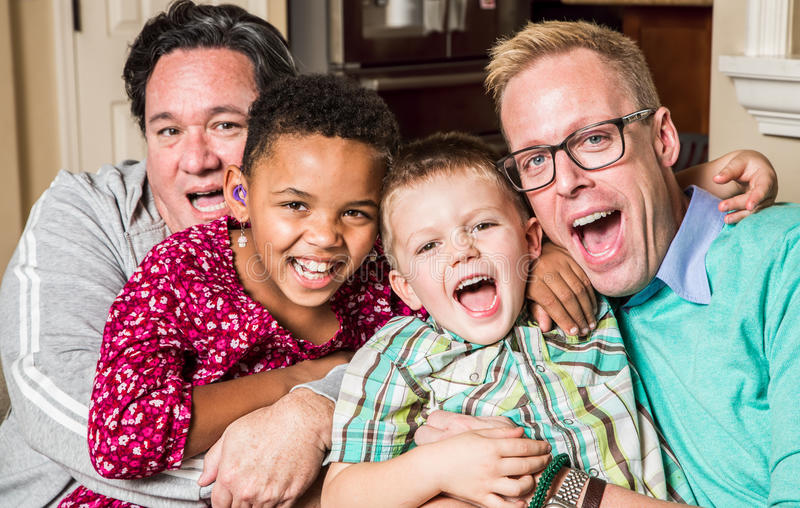 Gay Parents With Chidren. Gay parents pose with their childen in the living room royalty free stock images