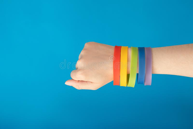 Rainbow flag LGBT wristband bracelet on female hand on blue background stock photography