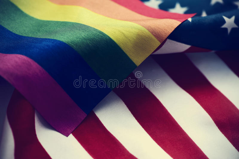 Gay pride flag and American flag. Closeup of a gay pride flag and a flag of the United States of America stock images