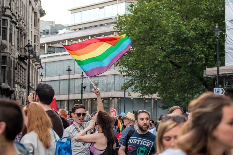 Gay Pride Parade, folla della gente con la bandiera d'ondeggiamento dell'arcobaleno dell'uomo fotografie stock libere da diritti