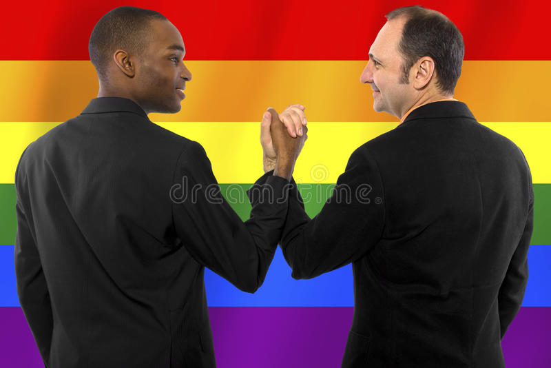 Gay Pride. Same-sex homosexual couple with a rainbow gay pride flag in the background royalty free stock image