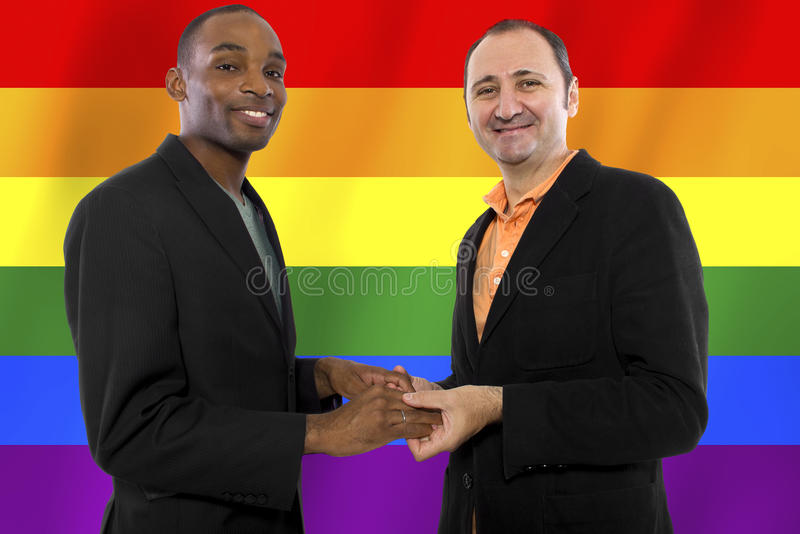 Gay Pride. Same-sex homosexual couple with a rainbow gay pride flag in the background stock photos