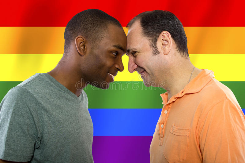 Gay Pride. Same-sex homosexual couple with a rainbow gay pride flag in the background stock image