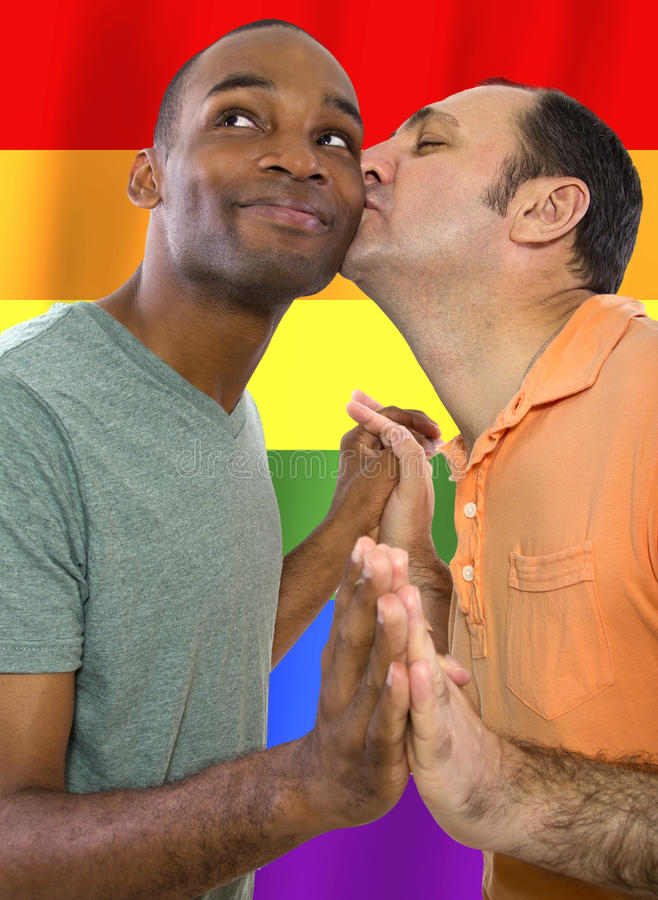 Gay Pride. Same-sex homosexual couple with a rainbow gay pride flag in the background royalty free stock images