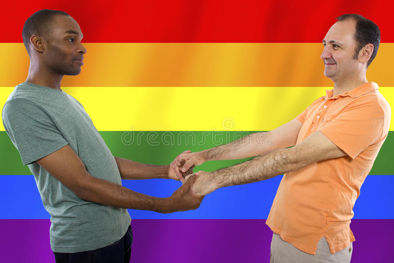 Gay Pride. Same-sex homosexual couple with a rainbow gay pride flag in the background royalty free stock photography