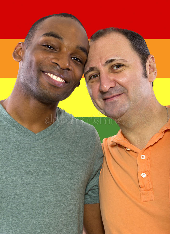 Gay Pride. Same-sex homosexual couple with a rainbow gay pride flag in the background stock photography