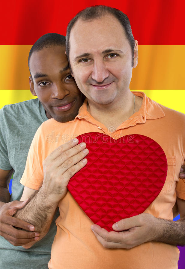 Gay Pride. Same-sex homosexual couple with a rainbow gay pride flag in the background stock photo