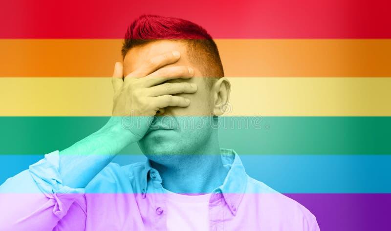 Gay que cubre su cara a mano sobre bandera del arco iris imagen de archivo