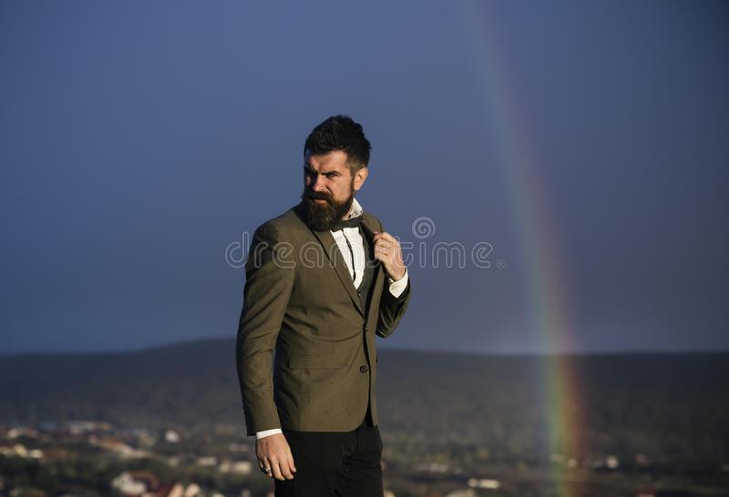 Gay and rainbow on blue sky. Gay with beard in classic coat with bow tie on vacation stock photography