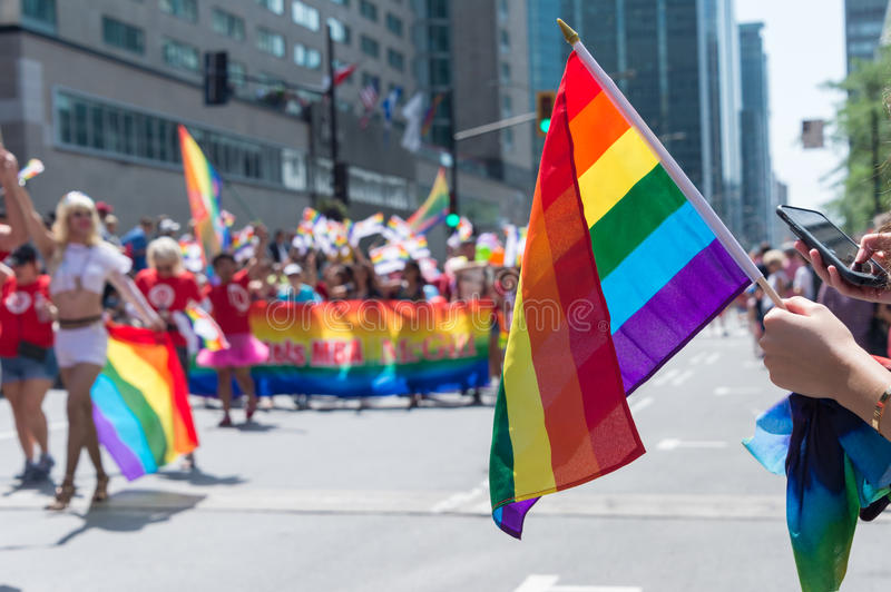 Gay rainbow flag at Montreal gay pride parade. Montreal, CANADA - 20 August 2017: Gay rainbow flag at Montreal gay pride parade with blurred participants in the royalty free stock photography