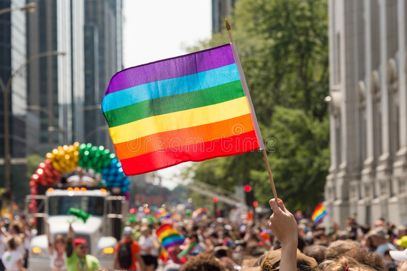 Gay rainbow flag at Montreal gay pride parade. Montreal, CANADA - 20 August 2017: Gay rainbow flag at Montreal gay pride parade with blurred participants in the royalty free stock photos
