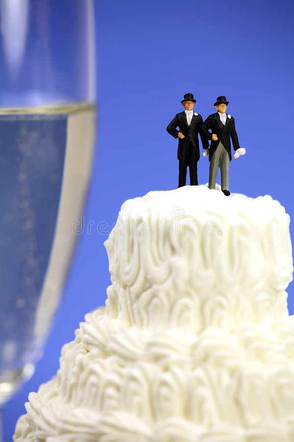 Gay or same-sex marriage concept. Miniature homosexual couple standing on top of a wedding cake. There is a glass of champagne in the background. Gay or same royalty free stock photos
