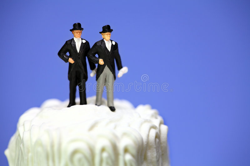 Gay or same-sex marriage concept. Miniature homosexual couple standing on top of a wedding cake. Gay or same-sex marriage concept royalty free stock photography