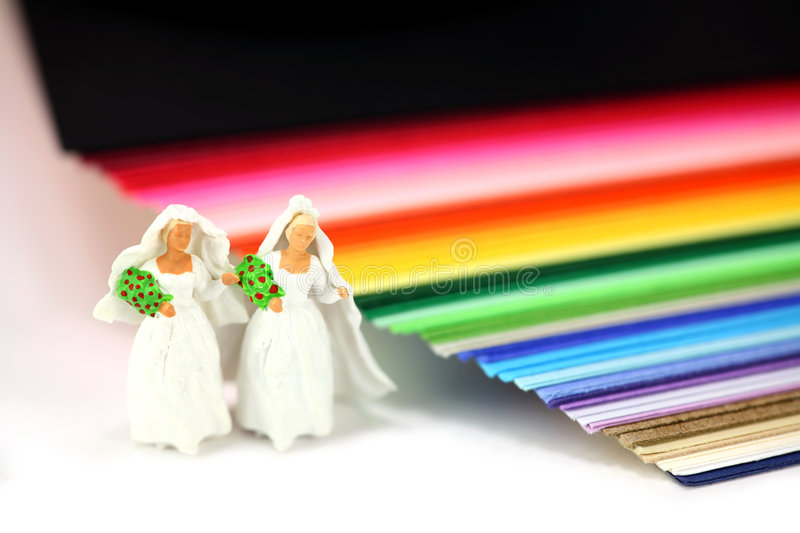 Gay or same-sex marriage concept. Miniature homosexual couple in wedding dresses standing next to rainbow colored paper. Gay same-sex marriage concept royalty free stock photography