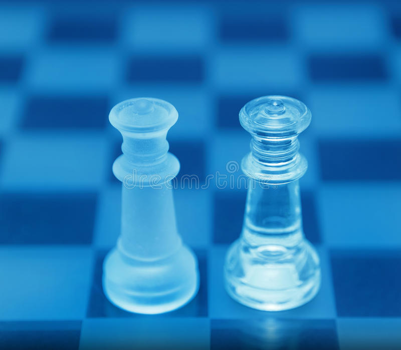 Gay marriage. Gay / same sex marriage depicted by two blue crystal Queen chess pieces on a board, supporting concept royalty free stock image